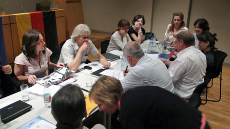 Many people sitting around a table covered with documents (Opens a Larger Version of the Image)