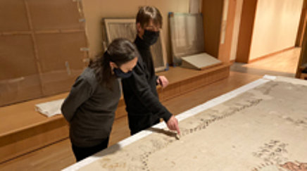 Two people look at a cotton cloth laying flat on a large table