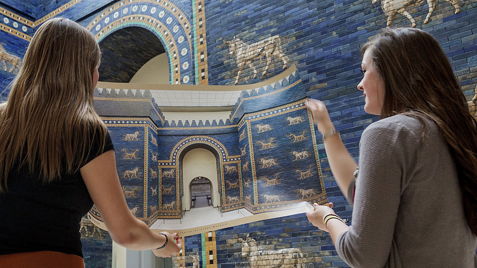 Two young women stand in front of the Ishtar Gate and hold a poster of the Ishtar Gate