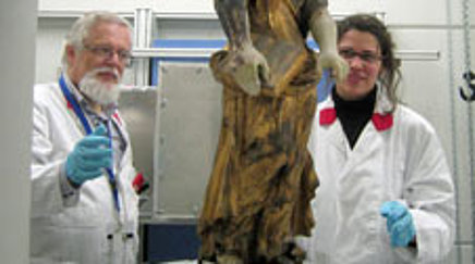 Two people in lab coats looking at a stone sculpture being examined with an instrument