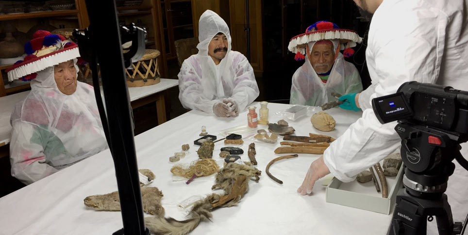 A delegation of elders of the Huichol, an indigenous people from Mexico, puts the collection of ritual objects from their ancestors in the Ethnologisches Museum back into the correct arrangement. The museum had lost this knowledge over the course of time.