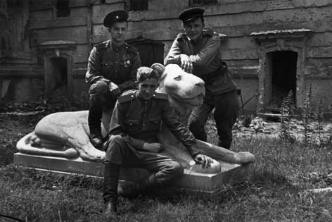 Three Red Army soldiers pose with the Mosse lion.