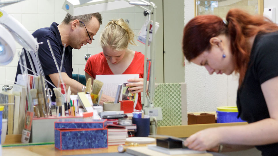 Two trainees and their trainer working on bookbinding