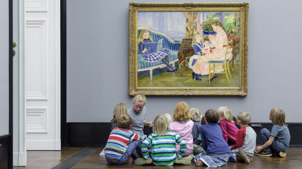 A woman and a group of children sit on the floor in front of a painting