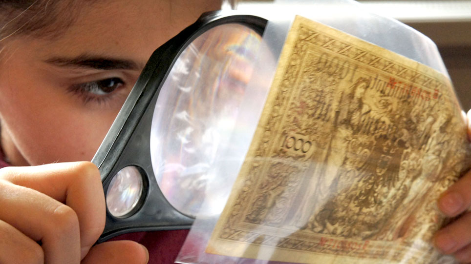 A child examines a bank note through a magnifying glass