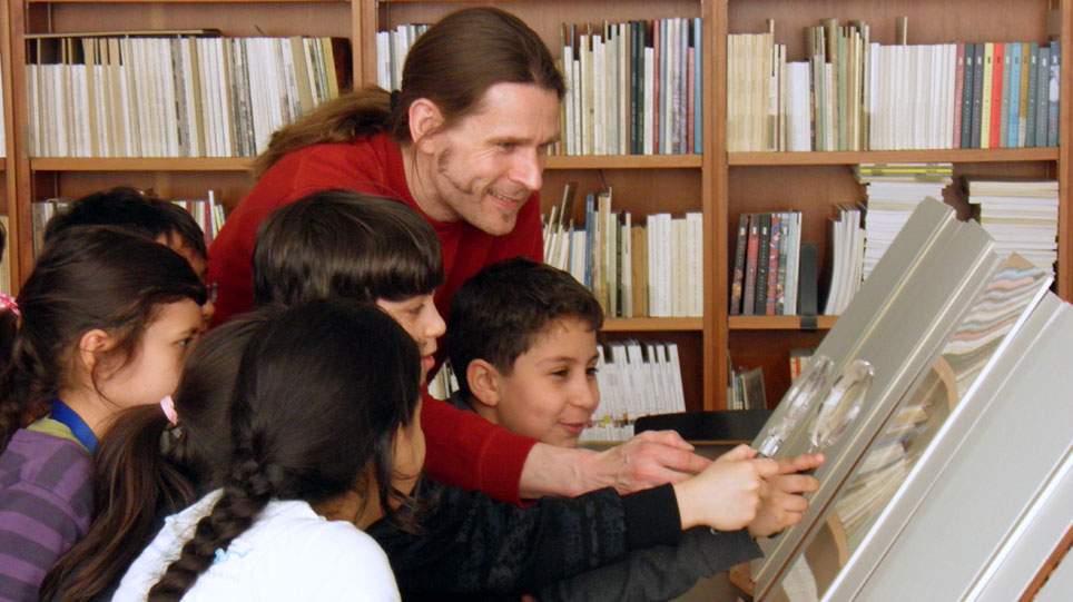 A man shows illustrations in a book to several children